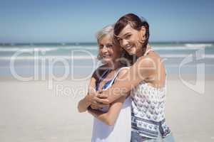 Portrait of happy woman embracing her mother at beach