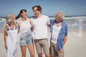 Happy family standing side by side at beach
