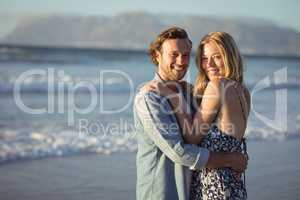 Portrait of smiling couple hugging at beach