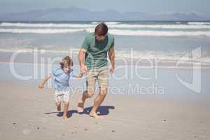 Happy boy with father running at beach