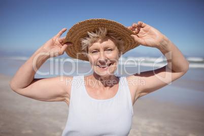 Portrait of senior woman wearing sun hat at beach