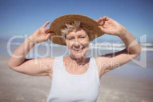 Portrait of senior woman wearing sun hat at beach