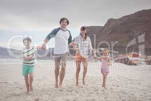 Portrait of family holding hands on sand at beach