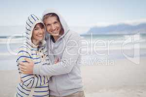 Portrait of smiling couple wearing hooded sweater during winter