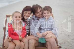 Happy family resting on lounge chairs