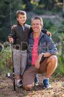 Father and son posing with fishing rod on field