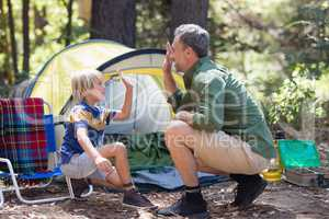 Father and son giving high five by tent at campsite