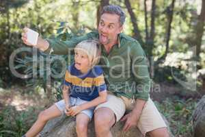 Father and son sticking out tongue while taking selfie in forest