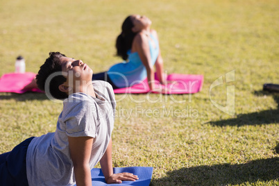 Boy and girl practicing yoga on mat