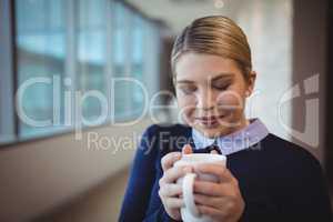 Beautiful executive smelling coffee