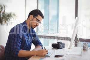 Graphic designer using graphic tablet at desk
