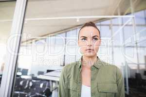 Thought businesswoman against glass wall