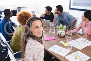 Portrait of businesswoman sitting with colleagues in meeting