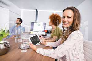 Smiling businesswoman using digital tablet while colleagues discussing in meeting