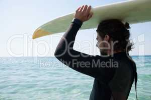 Surfer in wetsuit carrying surfboard over head at beach coast