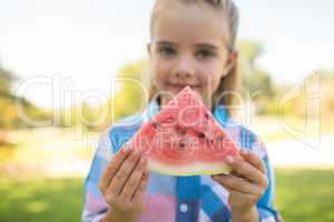 Girl holding watermelon slice in the park