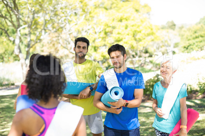 People with rolled exercise mats talking in the park