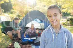 Girl smiling at camera while family sitting at tent in background
