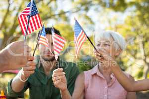 Family holding american flags in the park