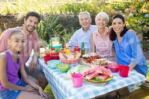 Family smiling at camera while having meal outdoors