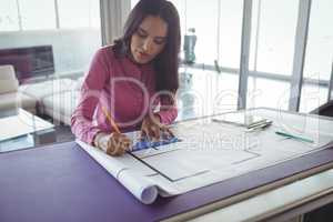 Female interior making diagrams on paper in office