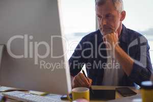 Focused businessman working on digitizer at office desk