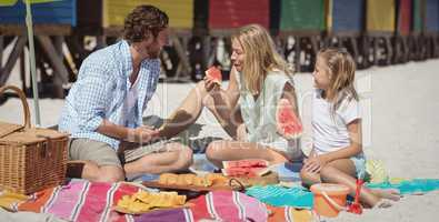 Happy family eating watermelon on blanket at beach