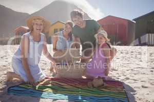 Portrait of happy multi-generation family by picnic blanket at beach