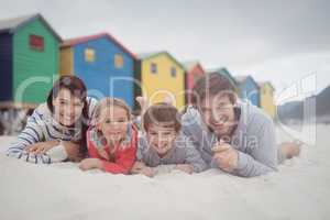 Portrait of smiling family lying on sand
