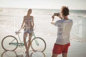 Man photographing woman standing by bicycle at beach