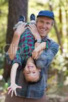 Playful father carrying son while hiking in forest