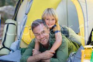 Little boy lying on father in tent at campsite