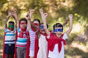Cheerful friends enjoying while wearing superhero costumes at campsite