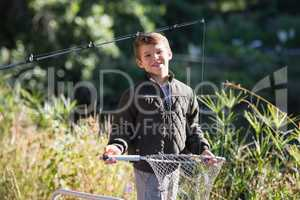 Portrait of smiling boy holding fishing net while standing in forest