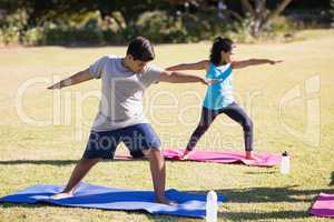 Kids practicing Virabhadrasana II on mat