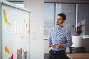 Thoughtful executive looking at whiteboard