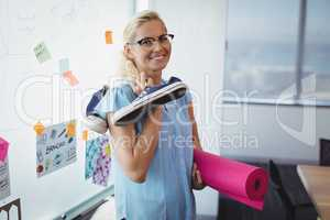 Portrait of smiling executive holding exercise mat and shoes