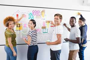 Portrait of business people sticking adhesive note during planning