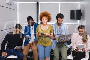 Portrait of businesswoman with colleagues using various technologies
