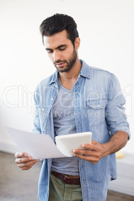 Businessman reading document while holding digital tablet