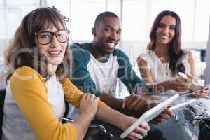 Portrait of smiling creative business colleagues using digital tablet