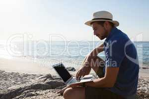 Man sitting on the rocks and using laptop on beach