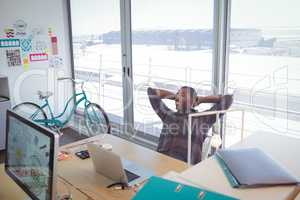 Businessman resting on chair in creative office