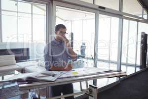 Male interior designer talking on mobile in office