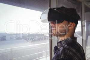 Young businessman wearing vr headset by window in office