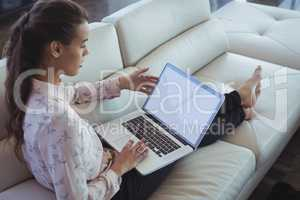 Businesswoman using laptop while resting on sofa