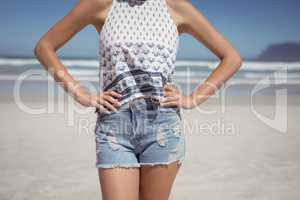 Mid section of woman with hands on hip standing at beach