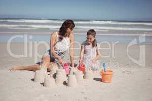 Happy girl with mother making sand castle at beach