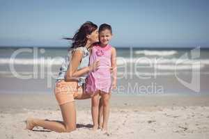 Happy mother kissing her daughter at beach