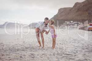 Girl kissing her mother standing at beach